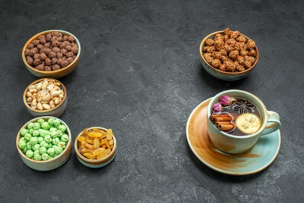 Vorderansicht verschiedene süße bonbons mit nüssen und tasse tee auf grauraum