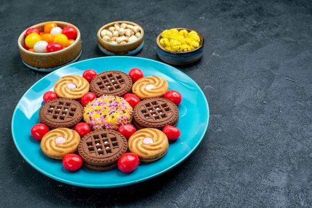 Vorderansicht verschiedene zuckerkekse mit bonbons auf grauer oberfläche zuckersüßigkeit süßer keksplätzchen