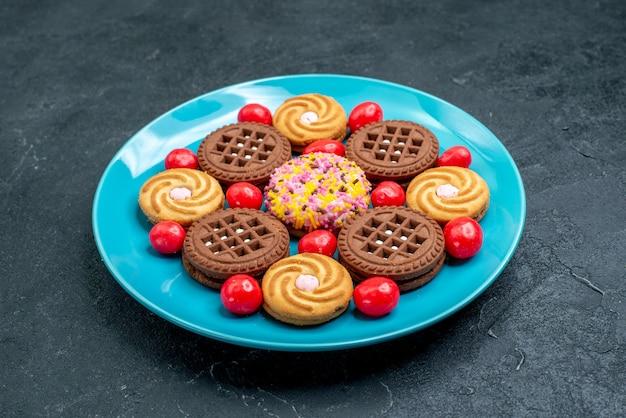 Vorderansicht verschiedene zuckerplätzchen innerhalb platte mit bonbons auf einer grauen oberfläche bonbonzucker süßer tee kekse keks