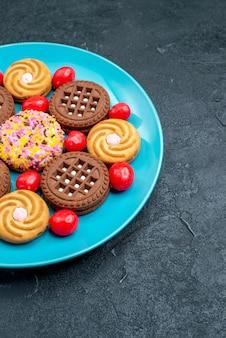 Vorderansicht verschiedene zuckerplätzchen mit bonbons auf der grauen oberfläche bonbonzucker süßer teeplätzchenkeks