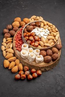 Vorderansicht verschiedener nüsse mit süßen konfitüren auf grauer oberfläche