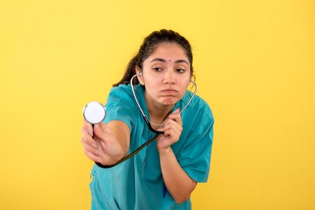 Vorderansicht verwirrte ärztin in uniform unter verwendung des stethoskops auf gelbem hintergrund