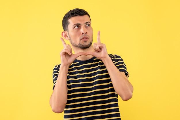Vorderansicht verwirrte gutaussehenden mann in schwarzem und gestreiftem gelbem lokalisiertem hintergrund des gestreiften t-shirts