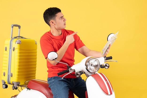 Vorderansicht verwirrte jungen mann auf moped, das karte hält, die etwas betrachtet