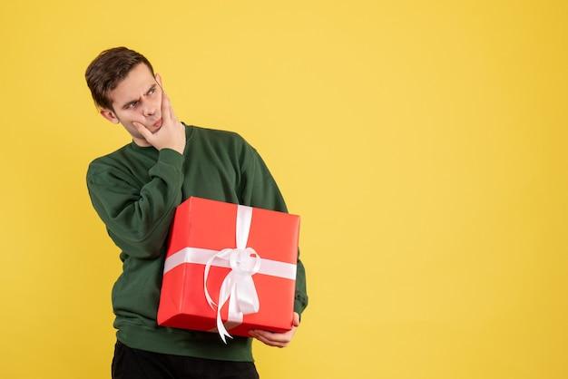 Vorderansicht verwirrte jungen mann mit grünem pullover, der auf gelb steht