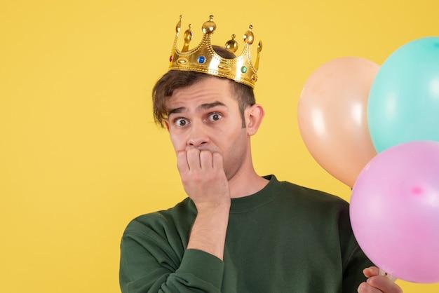 Vorderansicht verwirrte jungen mann mit krone, die luftballons auf gelb hält