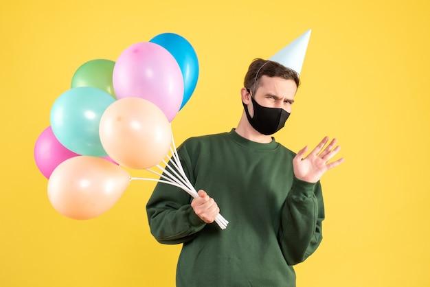 Vorderansicht verwirrte jungen mann mit partykappe und bunten luftballons, die auf gelb stehen