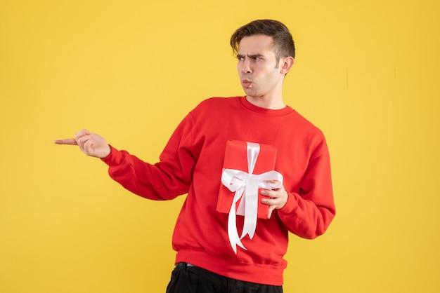 Vorderansicht verwirrte jungen mann mit rotem pullover, der etwas auf gelb zeigt