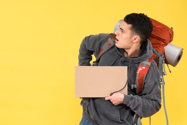 Vorderansicht verwirrte jungen mann mit rotem rucksack, der karton hält