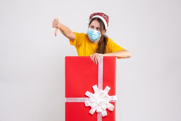 Vorderansicht verwirrte mädchen mit weihnachtsmütze, die daumen unten zeichen macht, das hinter großem weihnachtsgeschenk steht