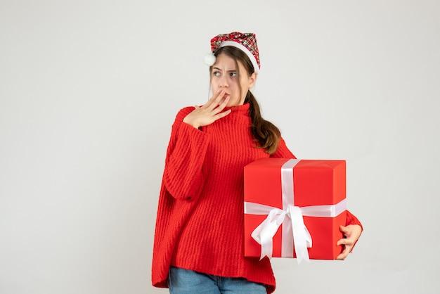 Vorderansicht verwirrte mädchen mit weihnachtsmütze, die gegenwärtige setzende hand hält