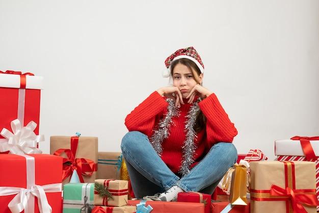 Vorderansicht verwirrte mädchen mit weihnachtsmütze, die um geschenke sitzt