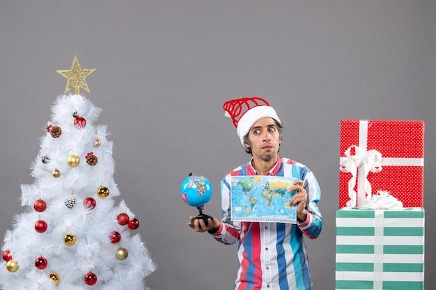 Vorderansicht verwirrte mann mit spiralfrühling santa hut, der weltkarte und globus um weihnachtsbaum und geschenke hält