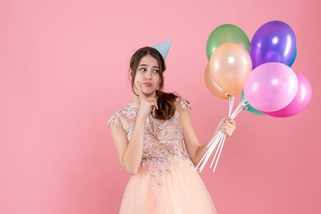 Vorderansicht verwirrte partygirl mit partykappe, die ballons hält
