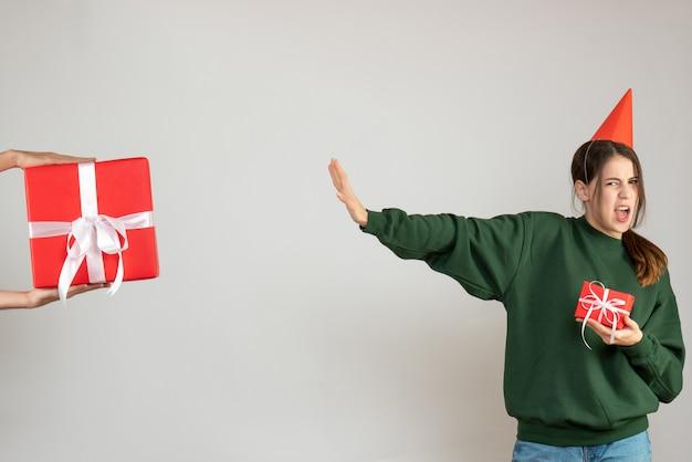Vorderansicht verwirrte partygirl mit partykappe, die ihr weihnachtsgeschenk hält, das menschliches hand haltendes geschenk ablehnt