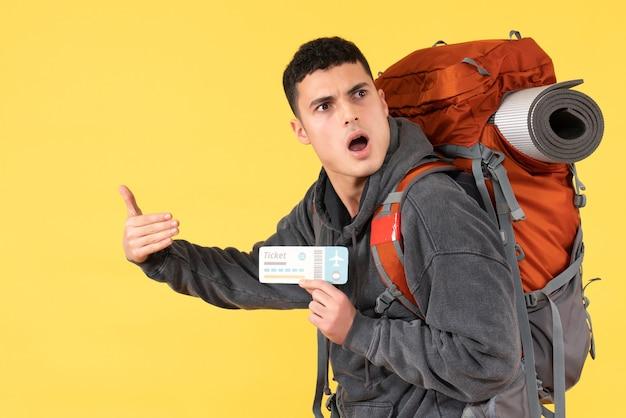 Vorderansicht verwirrte reisendenmann mit rucksack, der flugticket hält