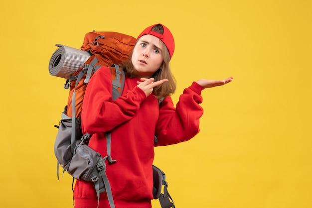 Vorderansicht verwirrte weibliche reisende mit rucksack, der etwas zeigt