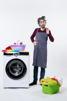 Vorderansicht verwirrter haushälter, der hand in die tasche steckt und in der nähe einer weißen waschmaschine auf weißem hintergrund steht