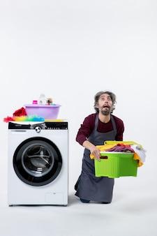 Vorderansicht verwirrter haushälter, der in der nähe der waschmaschine kniet und wäschekorb auf weißem hintergrund hält