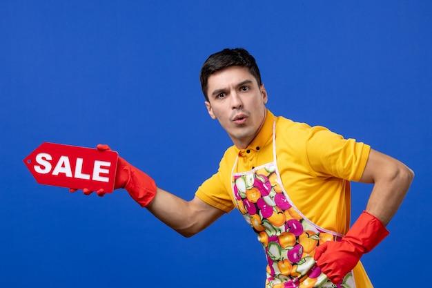 Vorderansicht verwirrter haushältermann im gelben t-shirt, das verkaufsschild auf blauem raum hält