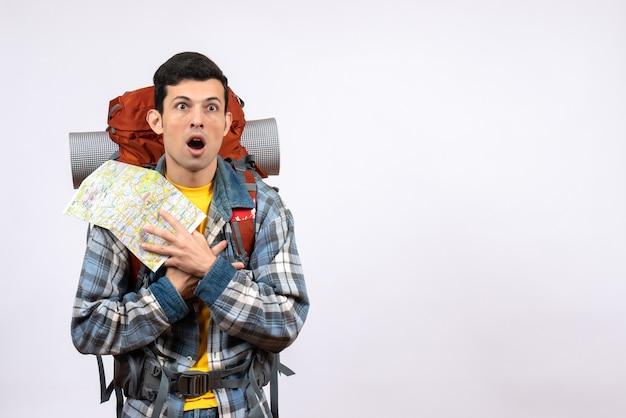 Vorderansicht verwirrter junger camper mit rucksack, der karte hält