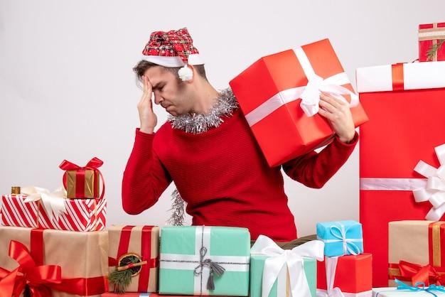 Vorderansicht verwirrter junger mann, der um weihnachtsgeschenke sitzt