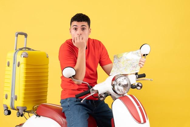 Vorderansicht verwirrter junger mann in der freizeitkleidung auf moped, das karte hält