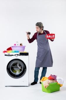 Vorderansicht verwirrter mann, der karte und verkaufsschild in der nähe des wäschekorbs der waschmaschine auf weißem, isoliertem hintergrund hält
