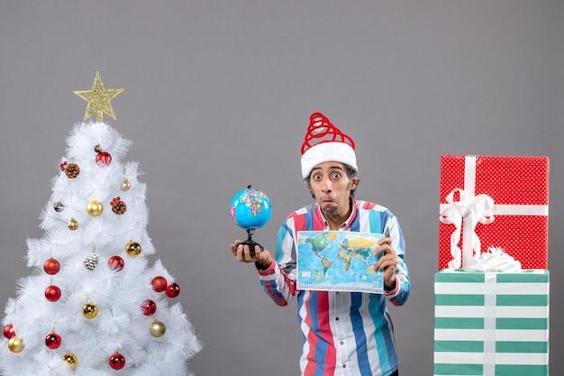 Vorderansicht verwirrter mann, der weltkarte und globus nahe weißem weihnachtsbaum mit weihnachtsspielzeug hält