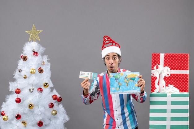 Vorderansicht verwirrter mann mit spiralfeder-weihnachtsmannmütze, die weltkarte und reiseticket hält