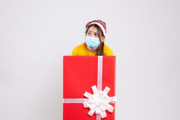 Vorderansicht verwirrtes mädchen mit weihnachtsmütze, die hinter großem weihnachtsgeschenk steht