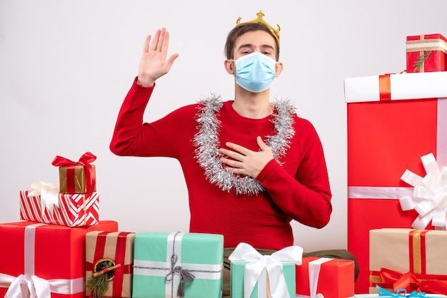 Vorderansicht vielversprechender schöner mann mit maske, die auf bodenweihnachtsgeschenken sitzt