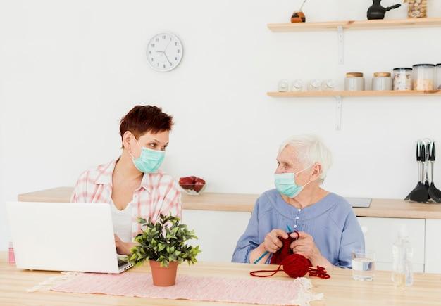 Vorderansicht von älteren frauen, die zu hause medizinische masken tragen, während aktivitäten ausgeführt werden
