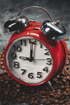 Vorderansicht von braunen kaffeesamen mit roter uhr dunkler oberfläche