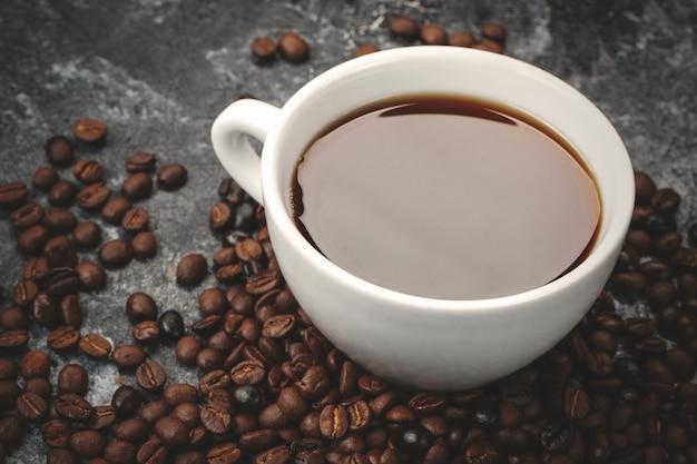 Vorderansicht von braunen kaffeesamen mit tasse kaffee auf dunkler oberfläche Premium Fotos