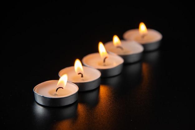 Vorderansicht von brennenden kerzen auf dunkler oberfläche