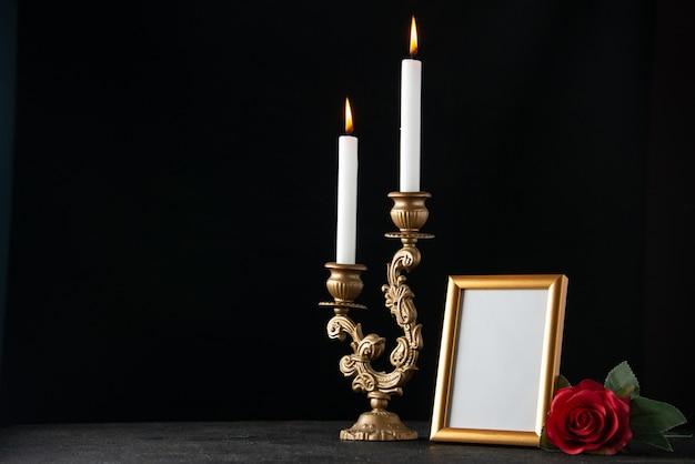 Vorderansicht von brennenden kerzen mit bilderrahmen auf dunkler oberfläche