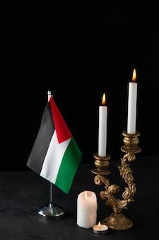 Vorderansicht von brennenden kerzen mit palästinensischer flagge auf dunkler oberfläche