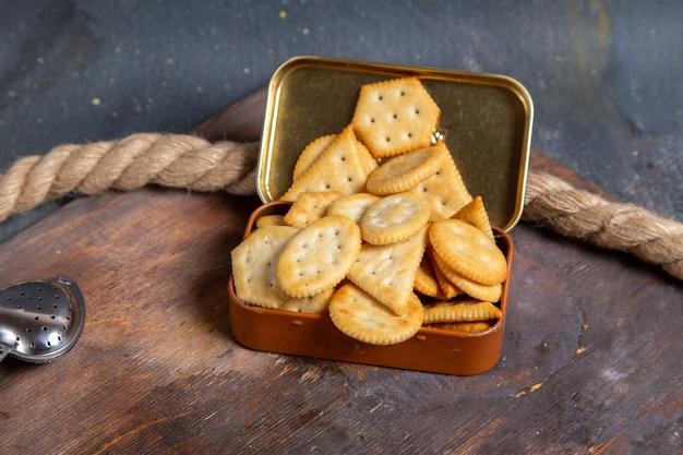 Vorderansicht von chips und crackern auf dem holzschreibtisch mit seilen