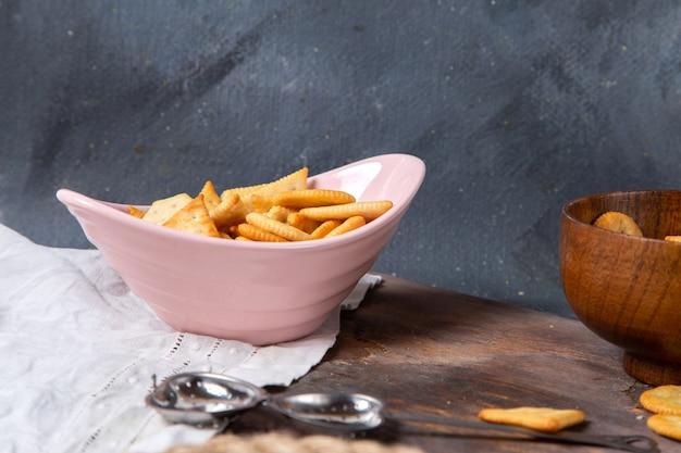 Vorderansicht von chips und crackern innerhalb der rosa platte auf der grauen oberfläche