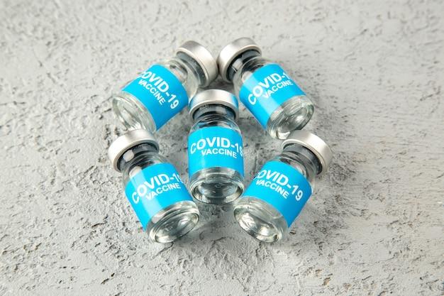 Vorderansicht von covid-impfstoffen auf grauem sandhintergrund mit freiem platz