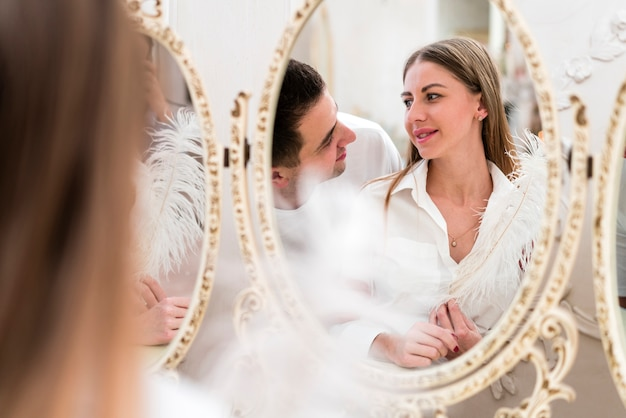 Vorderansicht von den paaren, die im spiegel mit feder schauen