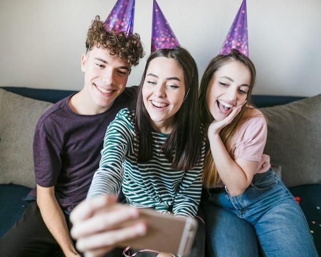 Vorderansicht von den smileyfreunden, die für ein selfie aufwerfen