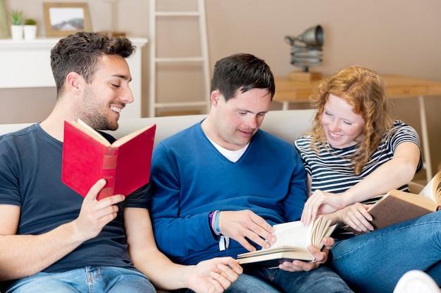 Vorderansicht von drei freunden, die auf sofa lesen