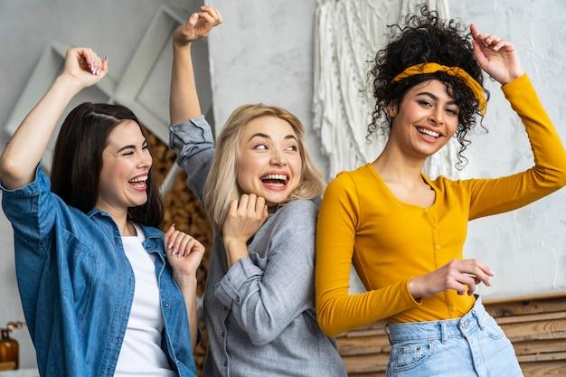 Vorderansicht von drei glücklichen frauen, die lächeln und tanzen