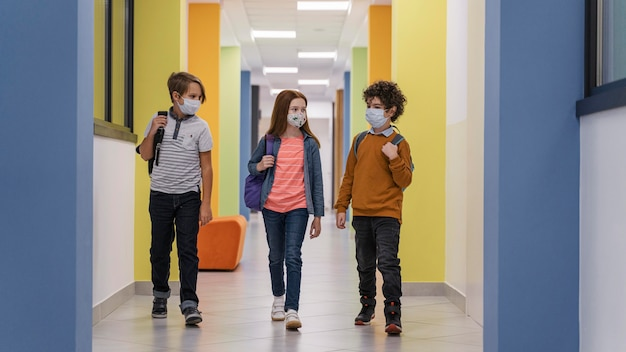 Vorderansicht von drei kindern auf schulflur mit medizinischen masken