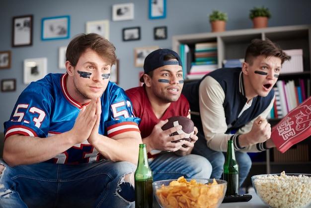 Vorderansicht von drei männern, die american football schauen