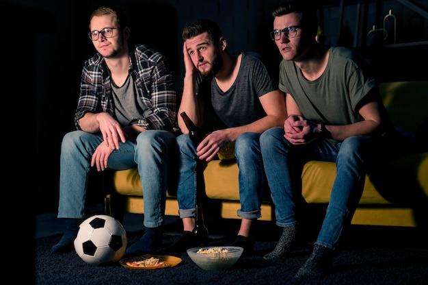 Vorderansicht von drei männlichen freunden, die zusammen sport im fernsehen schauen, während sie snacks und bier haben