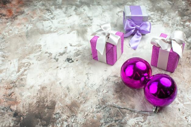 Vorderansicht von drei weihnachtsgeschenken für familienmitglieder und einem dekorationszubehör auf der linken seite auf eishintergrund