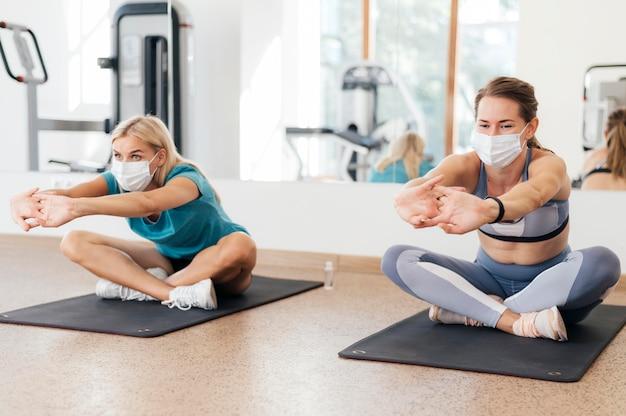 Vorderansicht von frauen, die während der pandemie im fitnessstudio zusammen trainieren